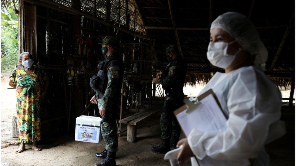 Uma trabalhadora de saúde municipal e um militar conversam com mulher indígena antes de ministrar uma vacina contra a covid nela no dia 9 de fevereiro de 2021, perto de Manaus