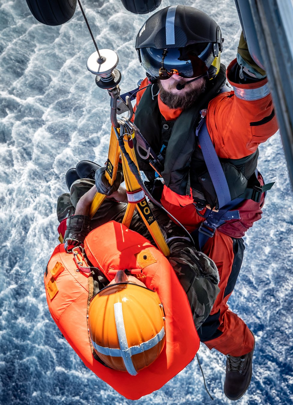 A pilot is winched onto a helicopter from the sea