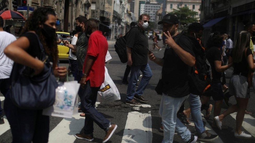 Pessoas caminhando em áres de comércio no Rio