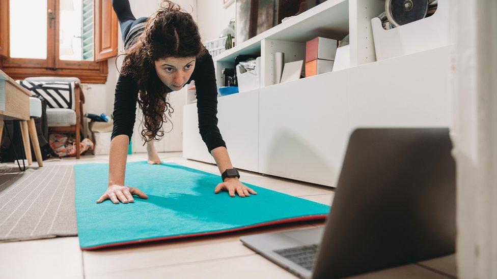 Una mujer se ejercita frente a una laptop