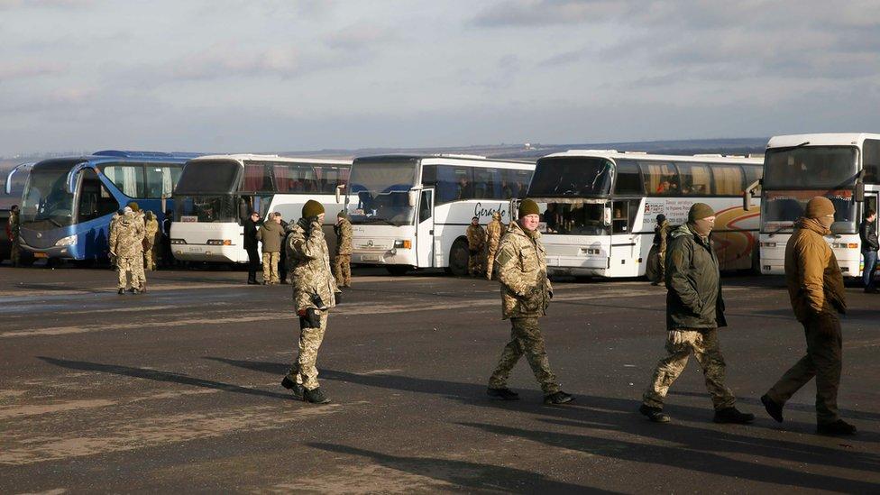 Servicemen of the Ukrainian armed forces gather near buses transporting prisoners near the city of Bakhmut in Donetsk region