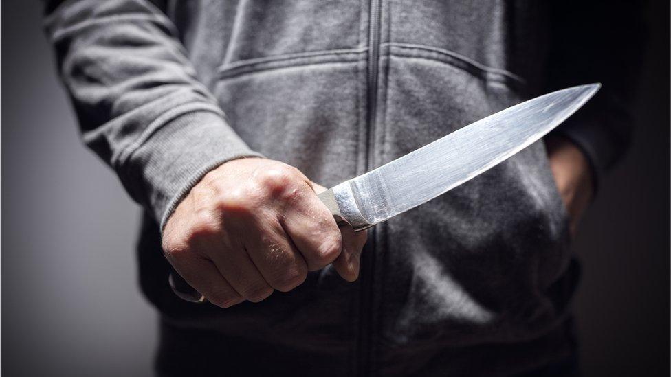 Stock image of man holding knife