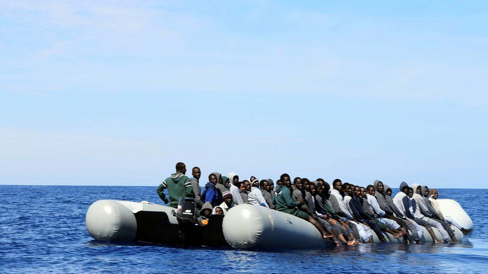 Migrants sit in their boat during a rescue operation by Italian navy ship Grecale off the coast of Sicily