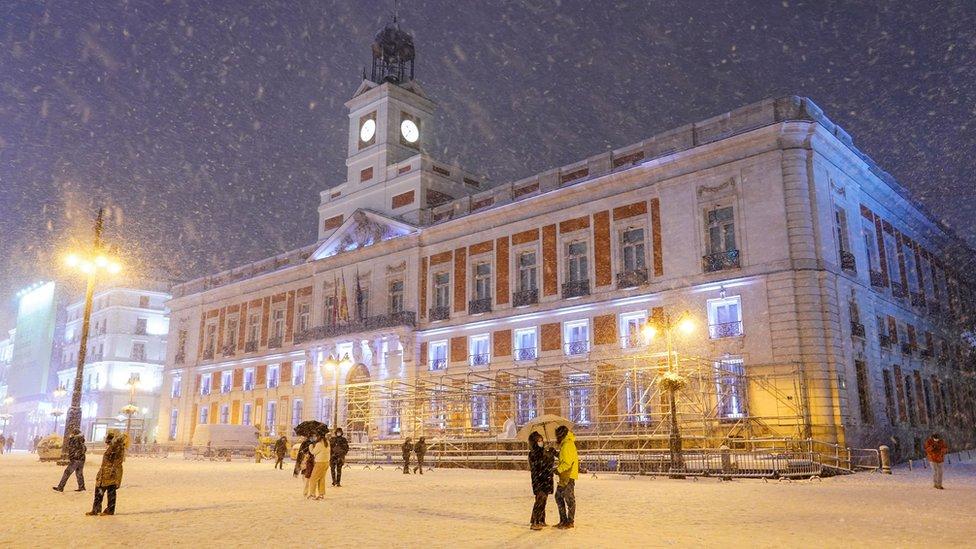 Gente camina en la nieve en la Puerta del Sol, Madrid