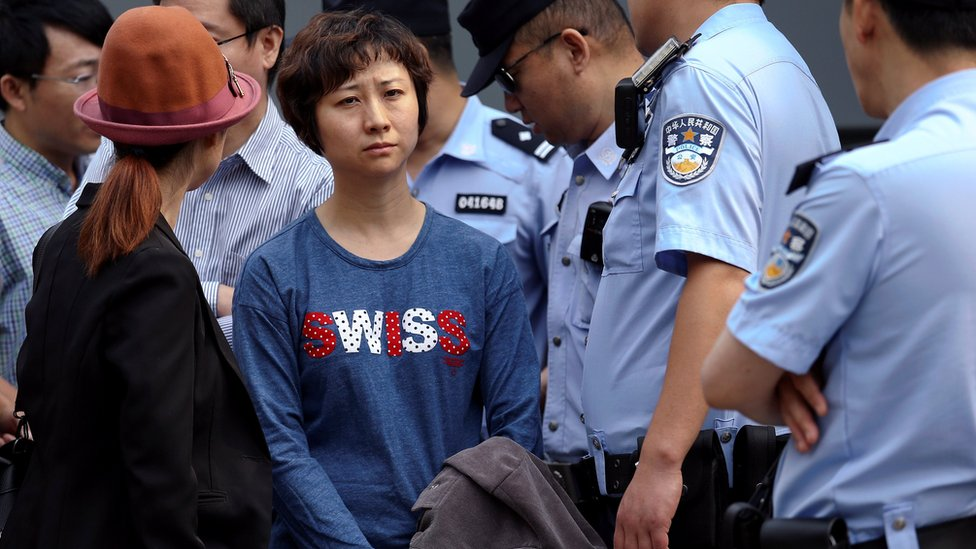 Policemen stand around Lin Ru, the wife of civil rights lawyer Xia Lin near the Beijing Number 2 People's Intermediate Court after her husband was sentenced to 12 years in prison on fraud charges in Beijing, China September 22, 2016