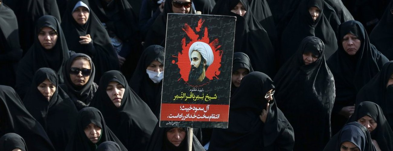 An Iranian woman holds up a poster showing Sheikh Nimr al-Nimr, a prominent opposition Saudi Shiite cleric who was executed last week by Saudi Arabia, in Tehran, Iran, Monday, Jan. 4, 2016.