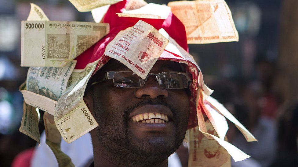 A man wearing a hat decorated with worthless notes, Harare, Zimbabwe - 2016