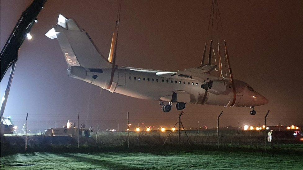 Avro RJ85 being lifted over road by cranes