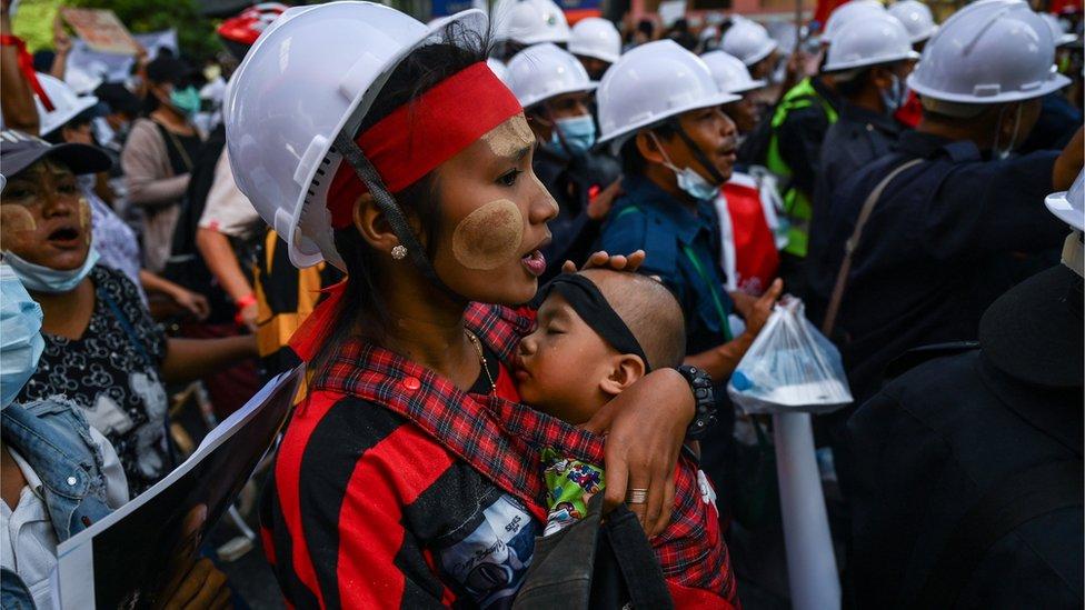 Seorang ibu yang ikut protes menggendong bayinya di Yangon.