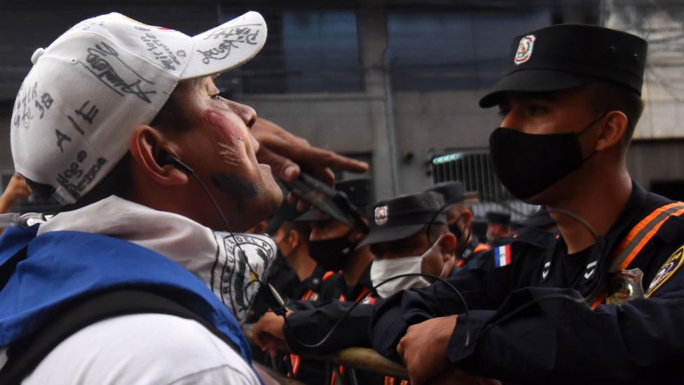 Un manifestante se enfrenta a un agente de seguridad en Paraguay.