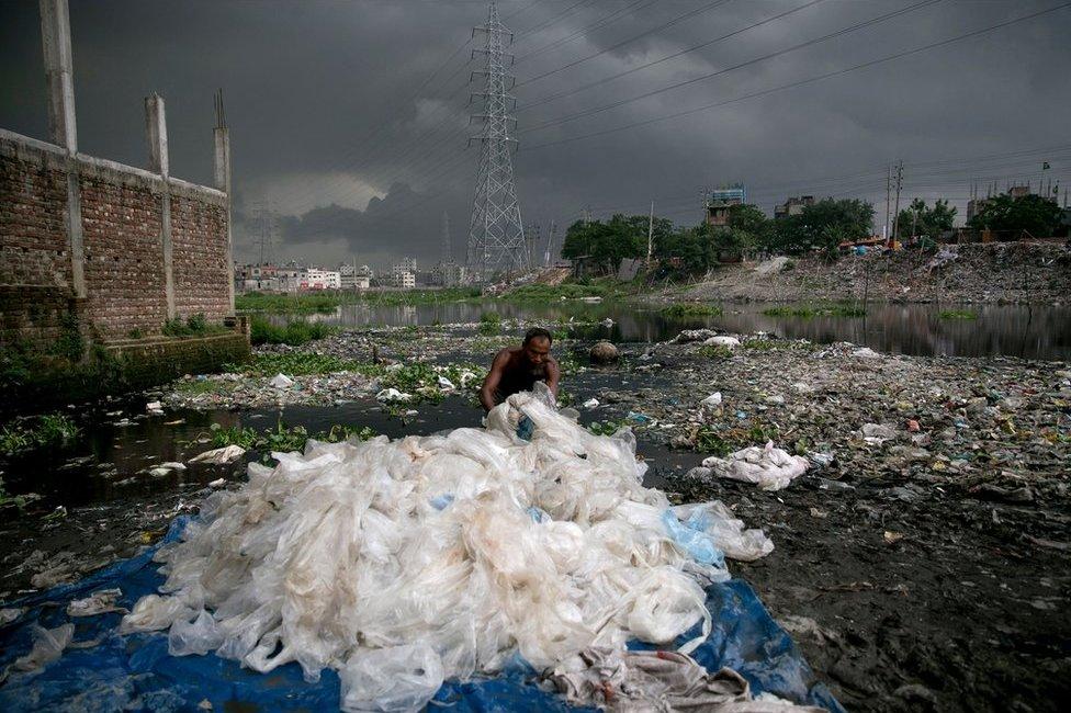 一名男子在一條運河中清洗經過化學處理的塑料袋。
