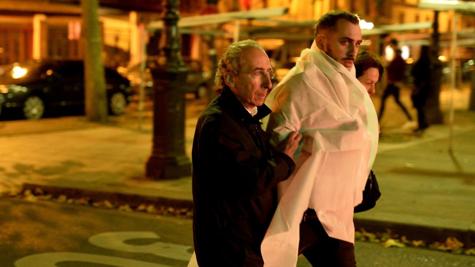A victim is escorted outside the Bataclan concert hall
