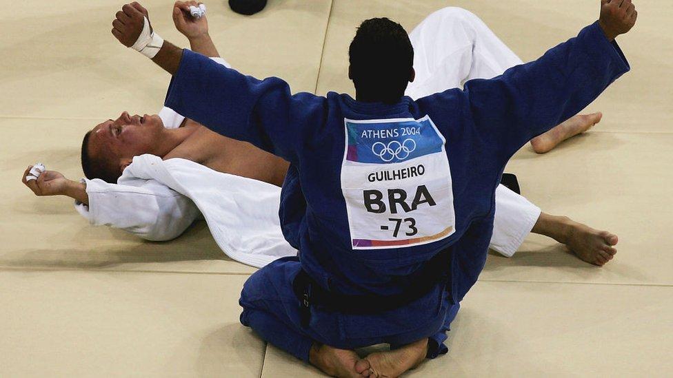 Leandro Guilheiro de Brasil (azul) celebra la victoria sobre Víctor Bivol de Moldavia (blanco) en la competencia por la medalla de bronce de judo masculino -73 kg durante los Juegos Olímpicos de Verano de Atenas 2004.