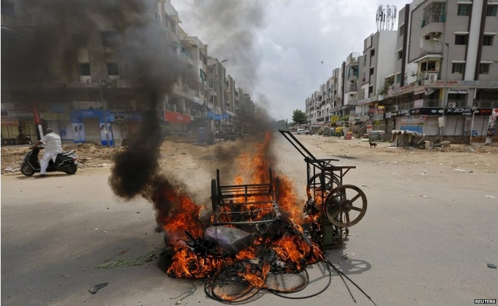 A man on a scooter stands next to burning vehicles after the clashes between the police and protesters in Ahmedabad, India, August 26, 2015.