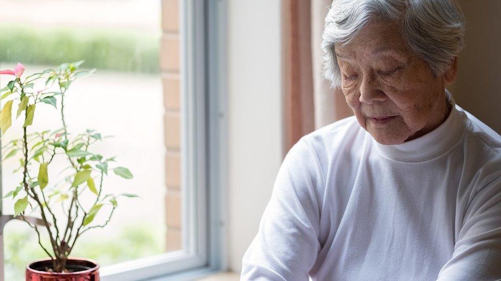 Starija žena pored prozora sedi zatovrenih očiju