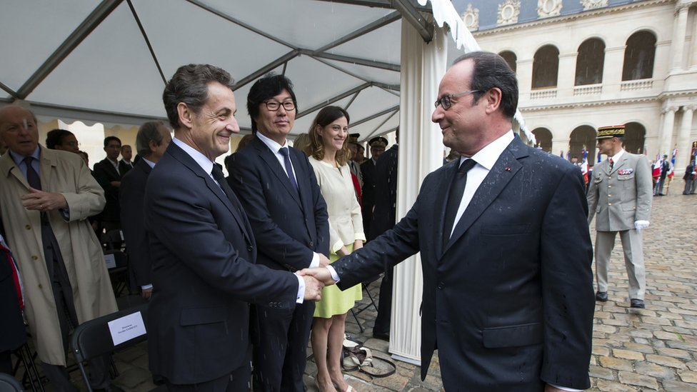 Francois Hollande, right, shakes hands with former French President Nicolas Sarkozy, 25 September 2016