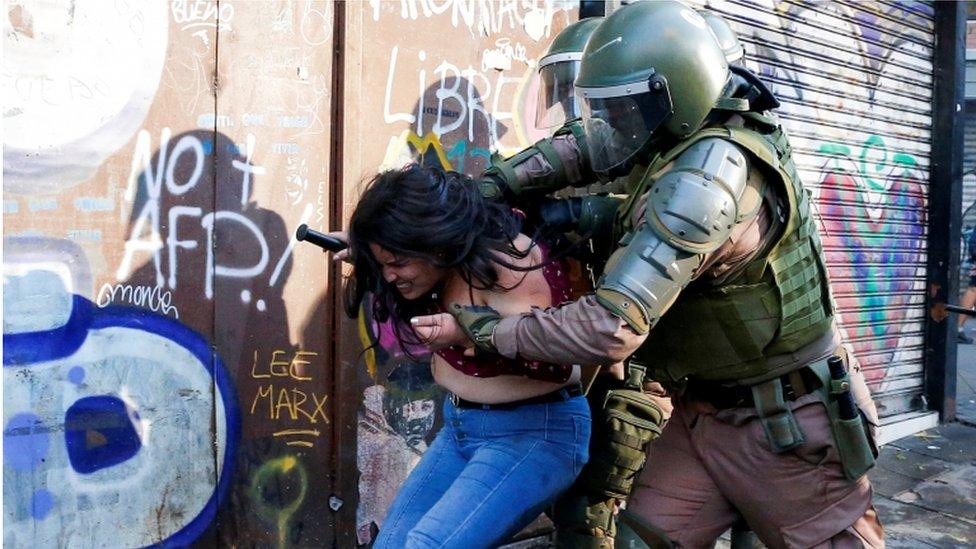 Mujer arrestada durante las protestas en Chile