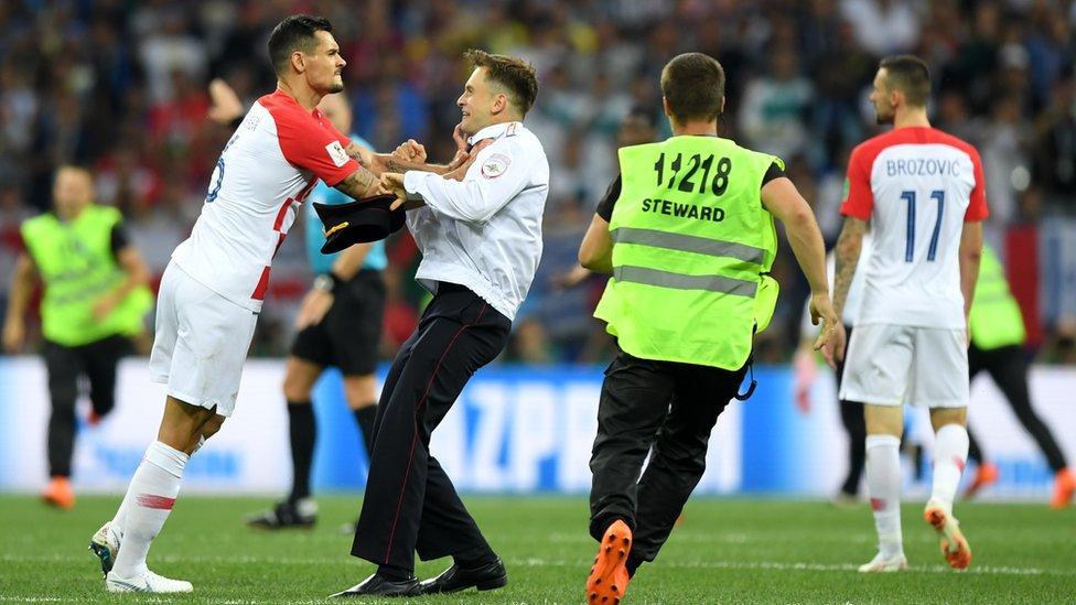 Jugador croata se enfrenta a una de las personas que irrumpió en el partido de forma inesperada.