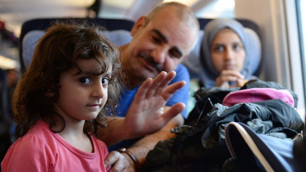 A migrant family from Syria sits in a special train at the train station in Munich, southern Germany, on September 13, 2015.