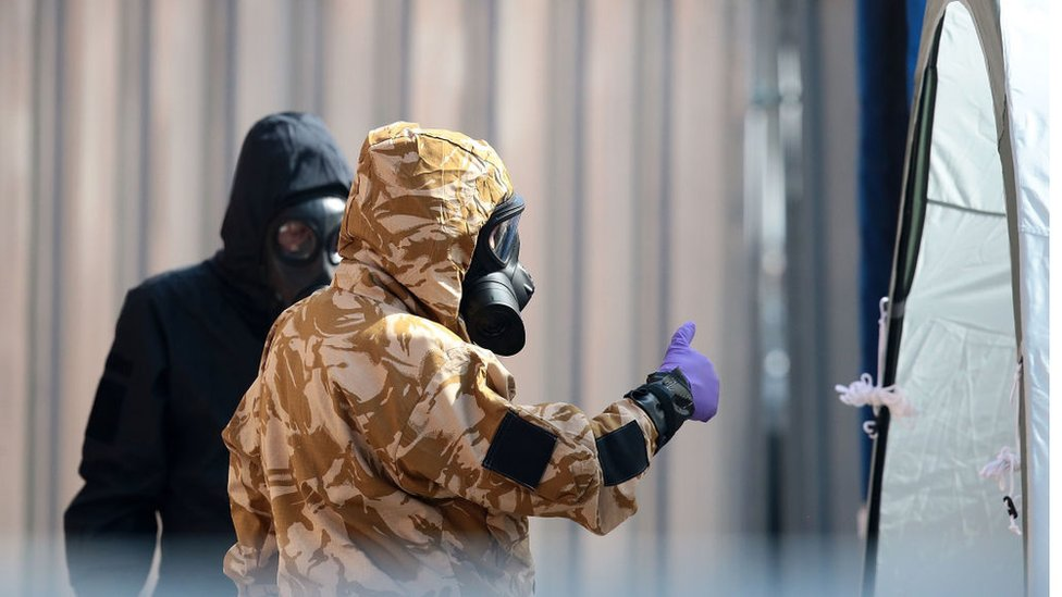 Emergency workers in protective suits search around a potentially contaminated site