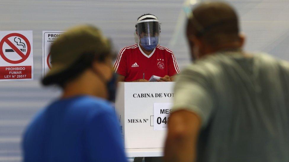 Dos personas de espaldas en un colegio electoral en Perú