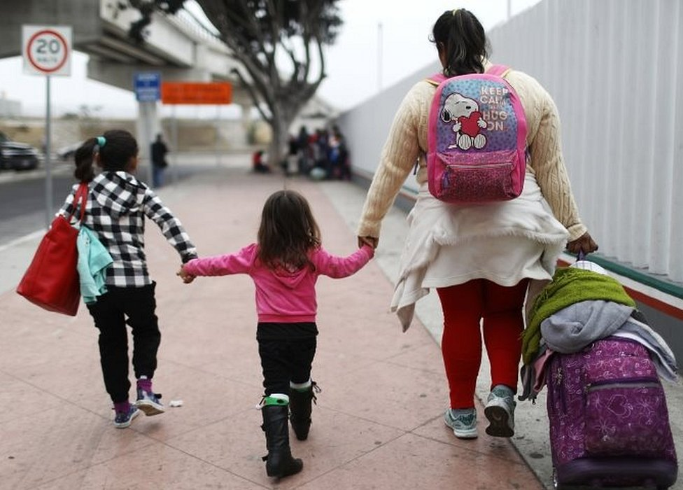 A migrant mother in Tijuana, Mexico, walks with her two daughters and their belongings on their way to the port of entry to ask for asylum in the US