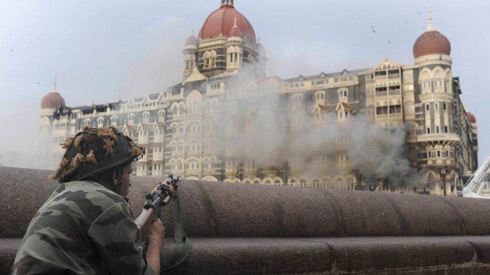 This photograph taken on November 29, 2008 shows an Indian soldier aiming his weapon towards The Taj Mahal Hotel in Mumbai.
