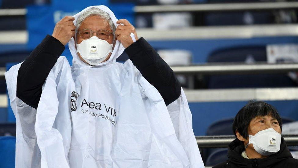 Güney Kore'de bir futbol maçında maskeli taraftarlar oyunu bekliyor