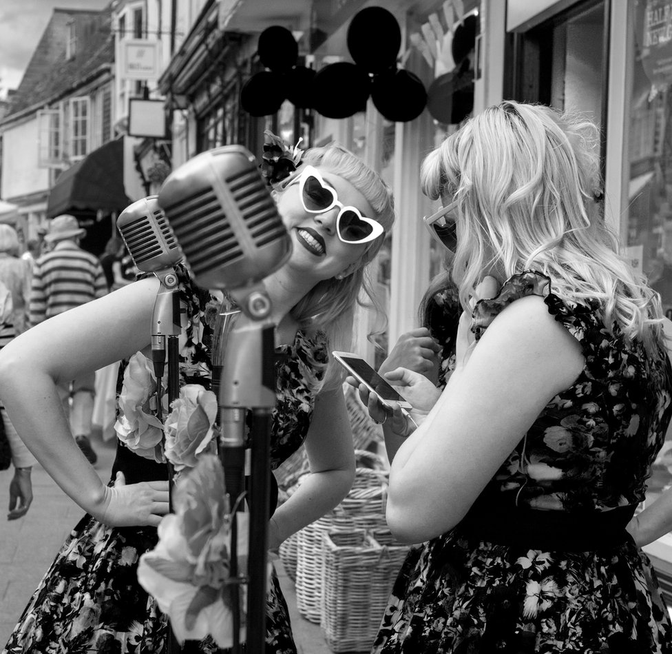 Two 1940s style singers are dressed in similar outfits. one is looking at her phone and the other at the camera