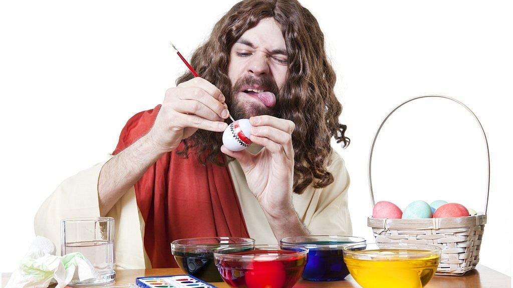 Hombre tratando de pintar un huevo con la lengua afuera