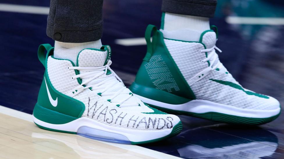 Seorang pemain basket mengenakan sepatu bertulisan