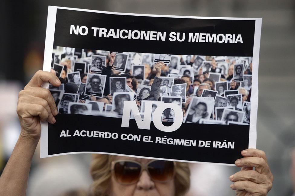 Una manifestante sostiene un cartel en contra del pacto con Irán