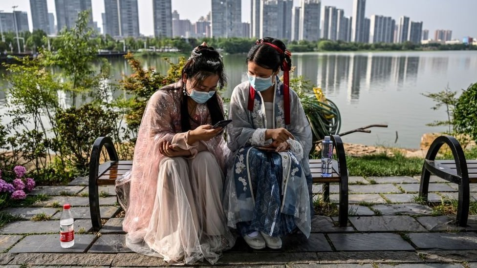 Two Chinese girls dressed in traditional ceremonial clothes look at their phones in the city of Wuhan