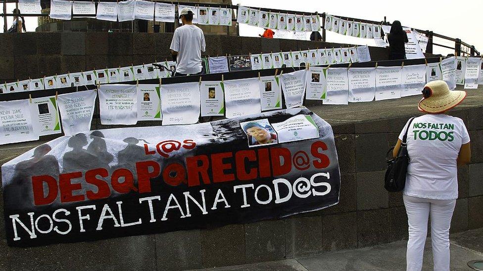 """Cartel en una plaza que dice """"Los desaparecidos nos faltan a todos""""."""