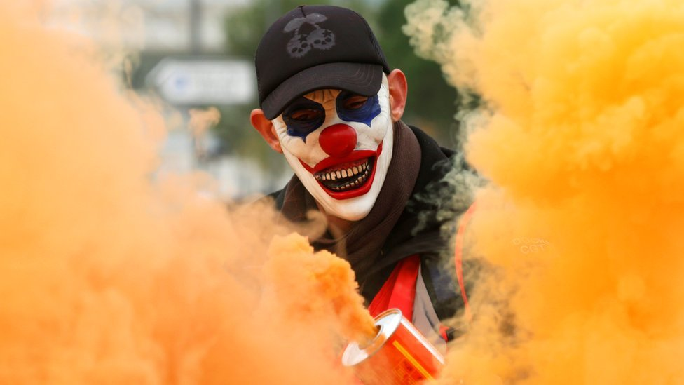 A protester wearing a mask is seen amongst smoke