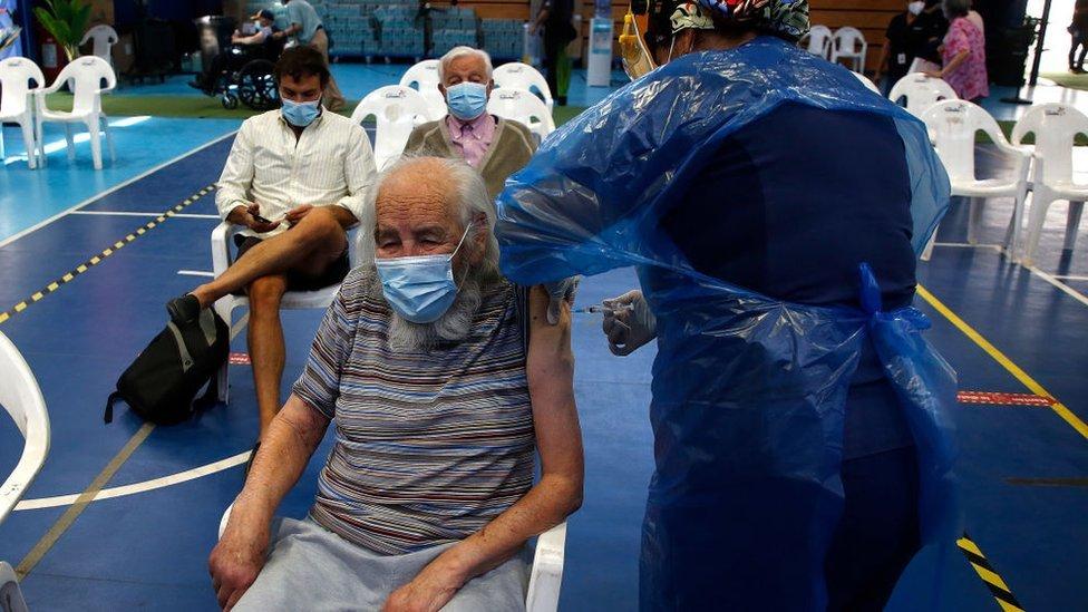 Pessoas recebendo a vacina em ginásio no Chile
