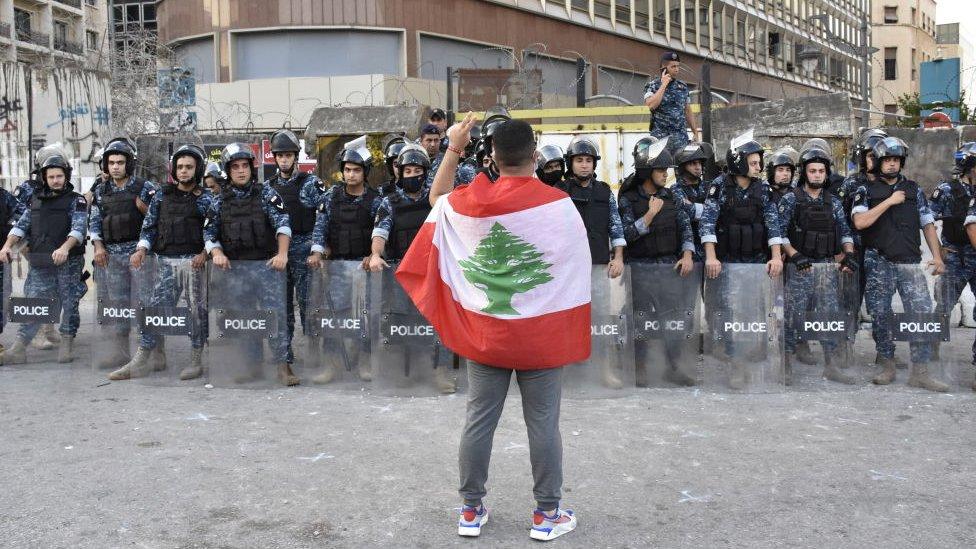 متظاهر يقف أمام القوى الأمنية في العاصمة اللبنانية بيروت، في يوليو/تموز 2020