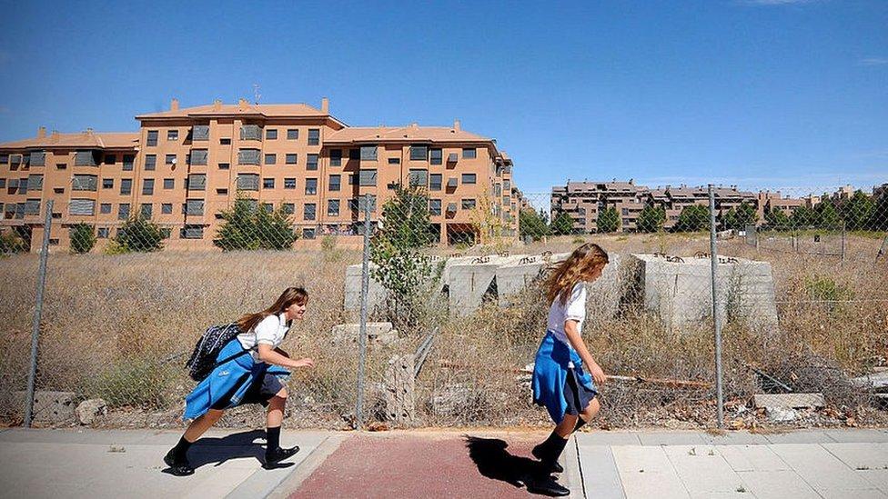 Two schoolgirls in front of unfinished apartment blocks in Valdeluz, Spain, in 2012