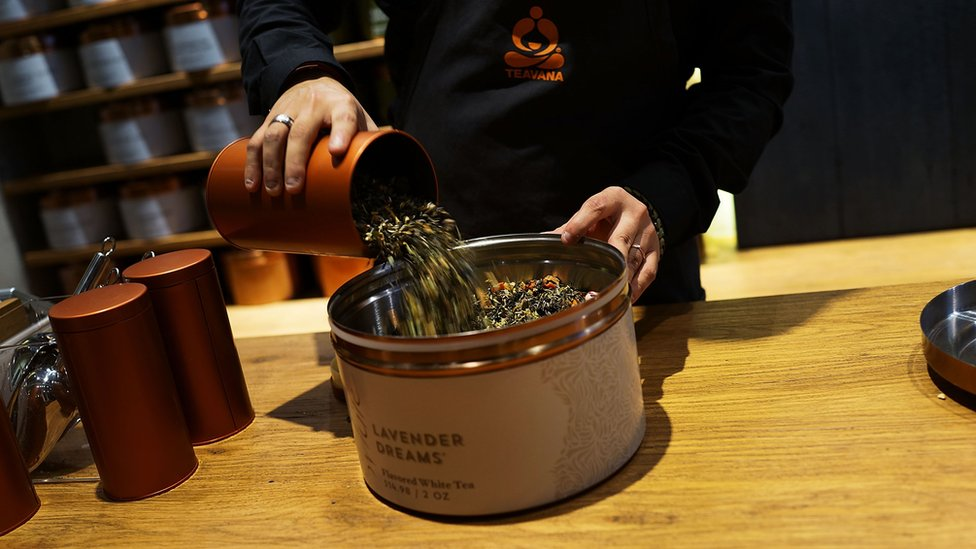An employee pours tea leaves at the newly opened Teavana 'tea bar' on October 24, 2013 in New York City