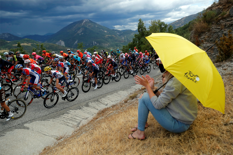 A woman holds an umbrella and watches professional cyclists cycle past
