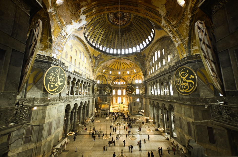 Interior of Hagia Sophia captured with fish-eye lens, warm light and unrecognizable people walking about.