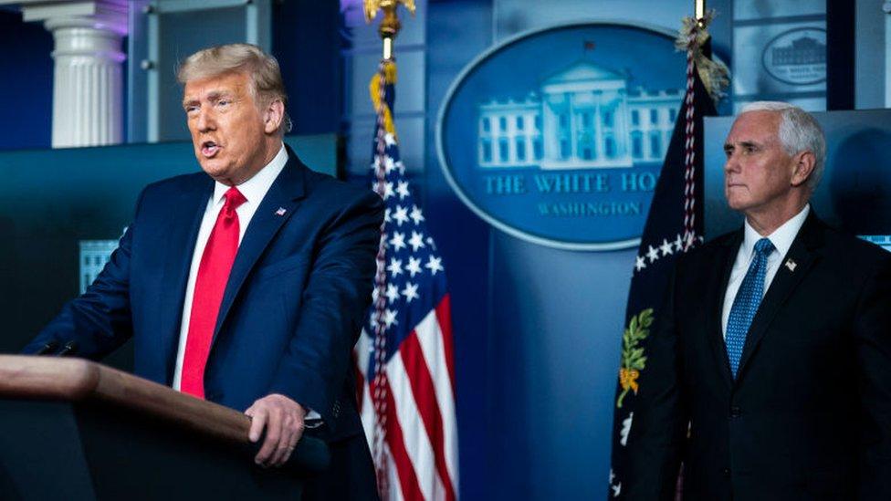 Mike Pence parado detrás del presidente Donald Trump durante una rueda de prensa