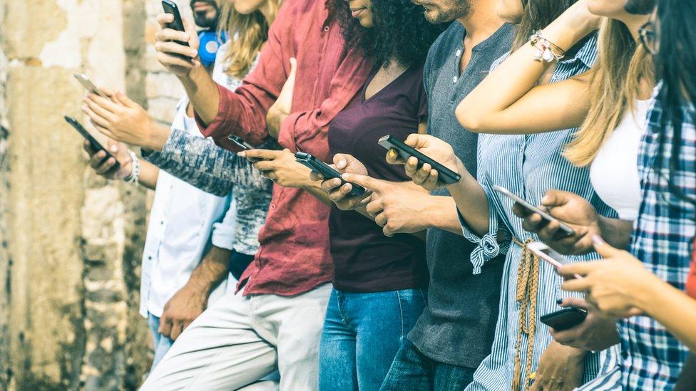 Grupo de amigos mirando el móvil.