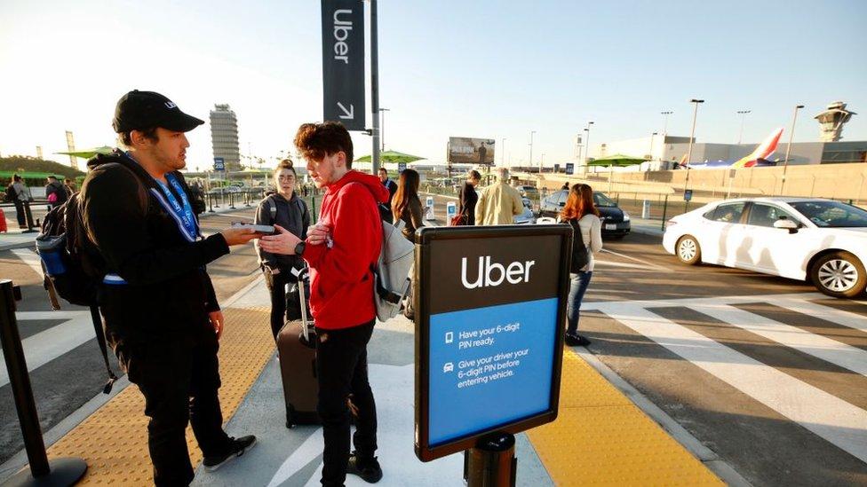 Pasajeros esperando un vehículo de Uber en un aeropuerto