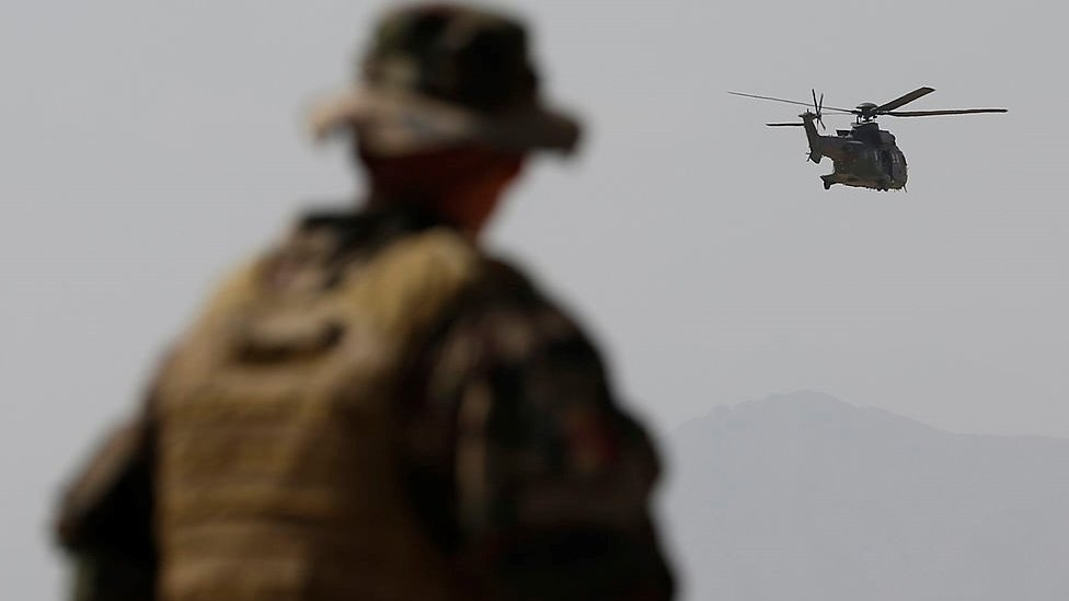 A French Army mentor looks on as a Eurocopter AS 532 Cougar helicopter of the French Helicopter Battalion 'Mousquetaire' flies