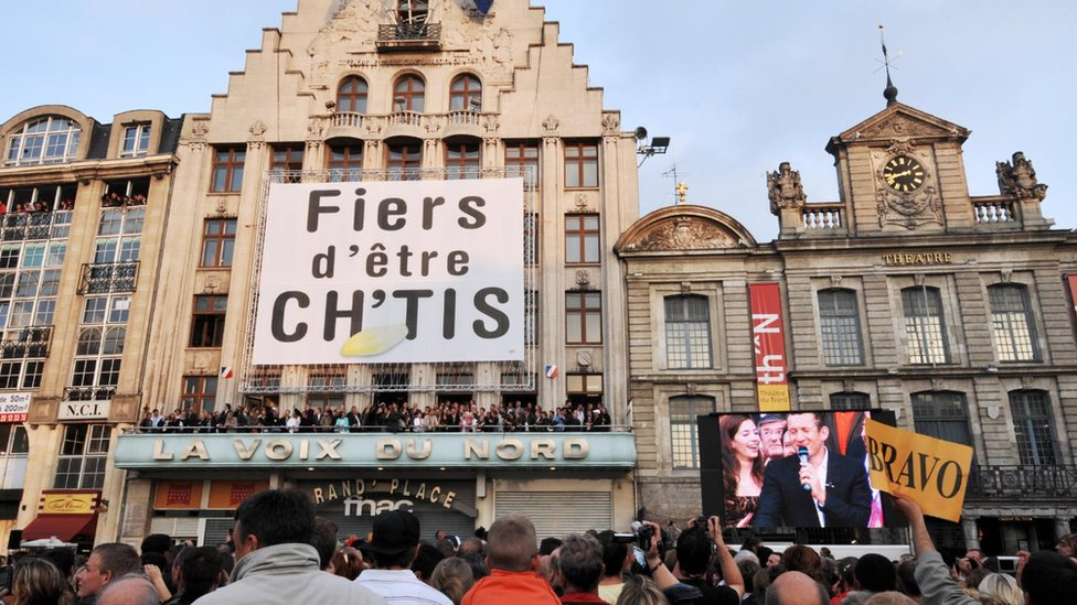Town hall in northern France with crowd and large banner reading les Ch'tis (Proud to be from the Sticks)