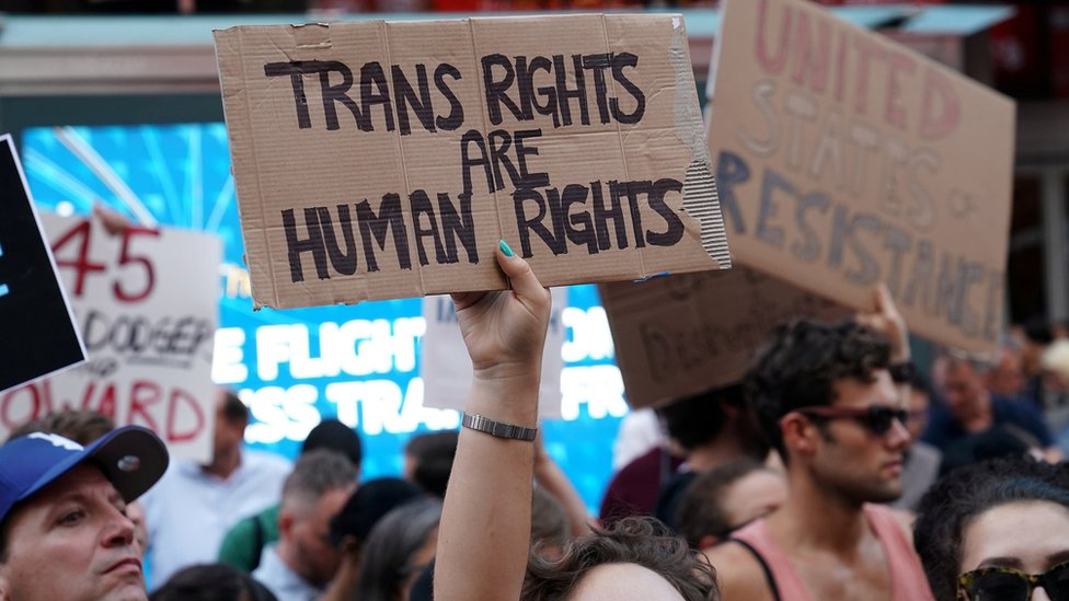 People protest President Trump's announcement of plans to reinstate a ban on transgender individuals from serving