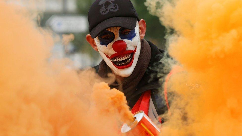 Manifestante con la cara pintada de payaso.