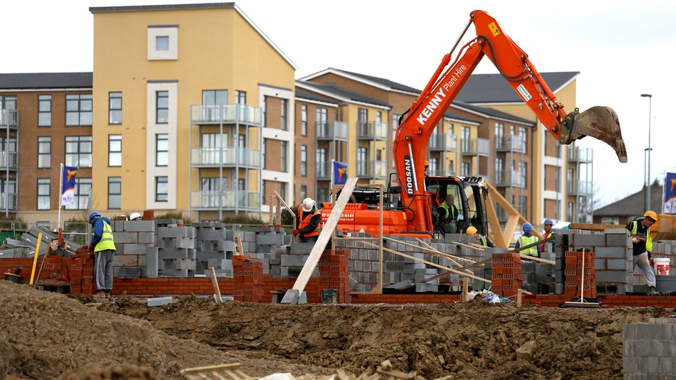 Building site with digger and new homes
