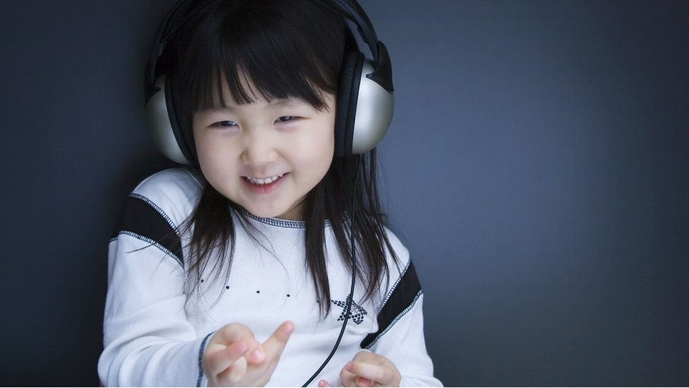 Child with headphones, fiddling with her fingers.